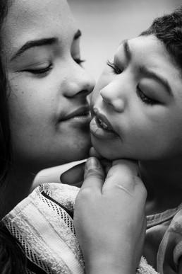 Sequência da foto anterior, nesta foto a jovem mulher está de perfil, com o rosto virado para o rosto da criança que está em seu colo. Seus rostos estão próximos um do outro, o queixo da jovem mulher encosta levemente no queixo da criança.