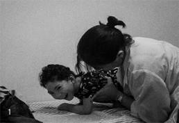 Foto em preto e branco. Uma criança sorridente está debruçada numa superfície coberta com um tecido. Uma mulher de jaleco e cabelo preto, liso e preso olha para a criança, enquanto segura seu tronco durante um manejo de cuidado.