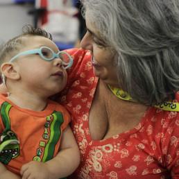 Foto colorida:Uma mulher de pele clara, cabelo ondulado, curto e grisalho, está com uma criança ainda bebê no colo. A criança tem a pele clara cabelos castanhos, ralos, curtos e usa óculos de grau com armação azul para crianças pequenas, os óculos ficam presos por trás da cabeça. A mulher sorri, ela e a criança se olham nos olhos.