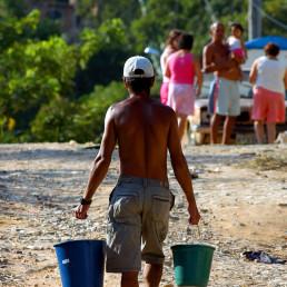 Foto colorida. Em uma rua de terra batida, um homem, de boné e bermuda e sem camisa, caminha de costas. Ele segura um balde em cada mão. Ao fundo, um grupo de pessoas e vegetação desfocadas.