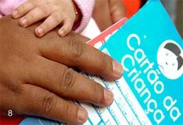 Foto colorida. Detalhe da Mão de uma pessoa de pele escura, que segura um cartão onde está escrito Cartão da Criança. A Mão de um bebê repousa sobre a mão adulta.