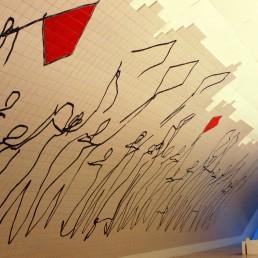 Foto colorida de uma parede arqueada do Museu de Arte Contemporânea de Niterói. Uma parte é coberta de azulejos brancos. Sobre eles, desenho abstrato em linhas pretas, como se traçado a mão, lembra uma fileira de pessoas lado a lado. Algumas soltam pipas brancas e vermelhas. Na parte de cima, o acabamento dos azulejos segue o desenho.