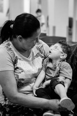 Foto em preto e branco de uma mulher sentada com uma criança no colo. Com o braço esquerdo ela apoia o tronco e a cabeça da criança. Ela e a criança olham uma para a outra. A mulher tem o cabelo preto, liso e comprido, preso num rabo de cavalo, ela olha para a criança em seu colo. A criança, que nasceu com a síndrome congênita do vírus Zika, tem cabelos castanhos curtos, usa óculos e está com a boca aberta, com a face inclinada em direção ao rosto da mulher que lhe acolhe.