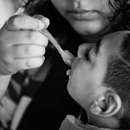 Foto em preto e branco de uma mulher que alimenta uma criança em seu colo. A mulher tem cabelos castanhos cacheados na altura do ombro, ela segura uma colher que está na boca da criança que tem os cabelos castanhos bem curtos passado à máquina.