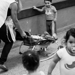 Foto em preto e branco registrada em ambiente escolar. Em primeiro plano, duas crianças levemente desfocadas, uma está com uma chupeta na boca, outra está de costas e só vemos a parte de trás de sua cabeça, com um rabo de cavalo. Ambas têm o cabelo preto. Atrás delas, uma mulher de cabelos lisos loiros e compridos, vestida com um guarda-pó segura o espaldar de uma cadeira de balanço pequena com uma criança com a síndrome congênita do vírus Zika deitada. Na frente delas, uma criança está de pé, sorrindo ao olhar para a criança que está na cadeira de balanço.