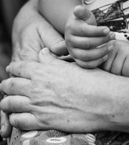 Foto em preto e branco das mãos de uma pessoa adulta que enlaçam a criança que está em seu colo. As mãos da criança estão apoiadas nas mãos da pessoa adulta.